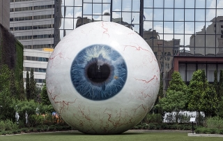 giant eyeball in front of large corporation